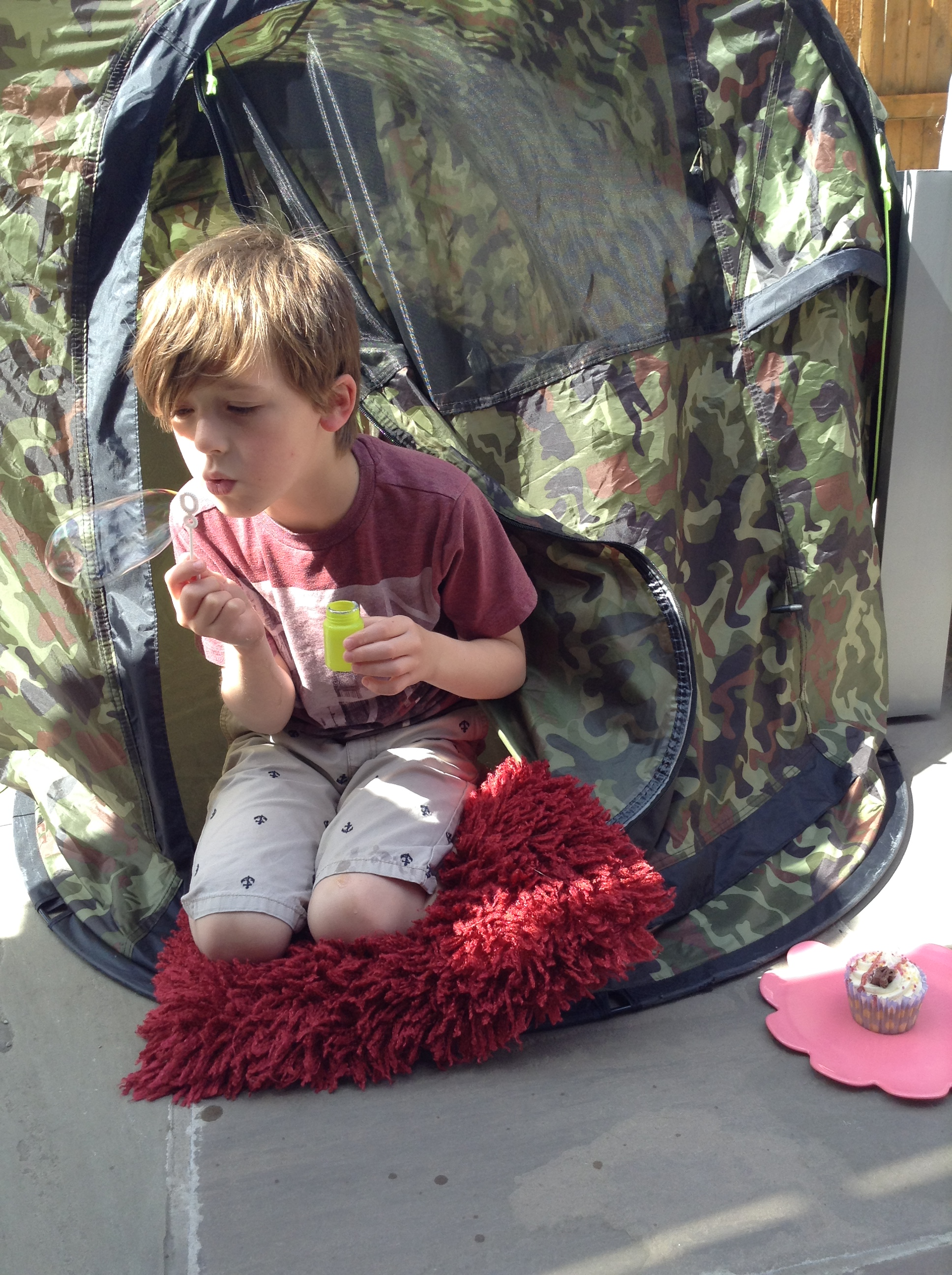 boy blowing bubbles in tent